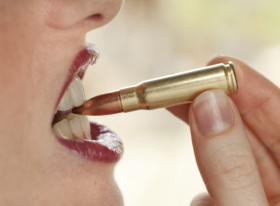 A woman literally biting a bullet