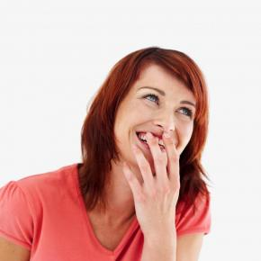 A woman covering her mouth while laughing