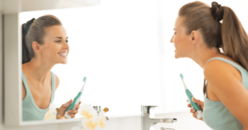 A woman looking in the mirror as she brushes her teeth