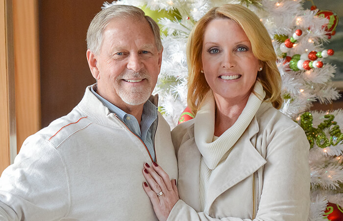 An older couple standing next to christmas tree