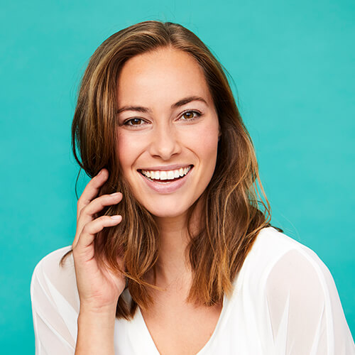 A woman smiling with a blue background