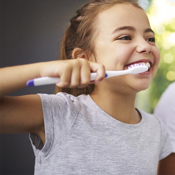 A little girl brushing her teeth properly