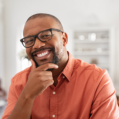 A man with glasses holding his face while smiling into the camera