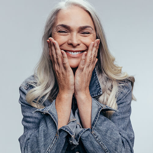 Woman with gray hair holding her face with joy