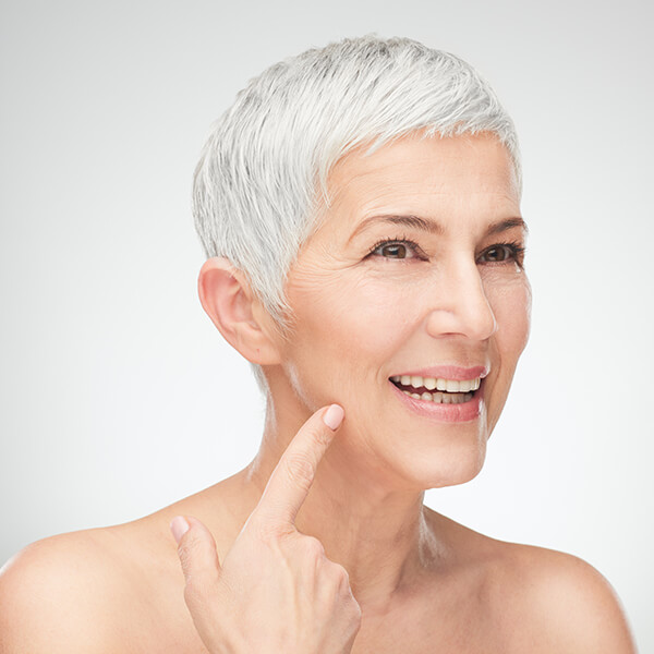 An older woman pointing at her smooth skin thanks to Botox