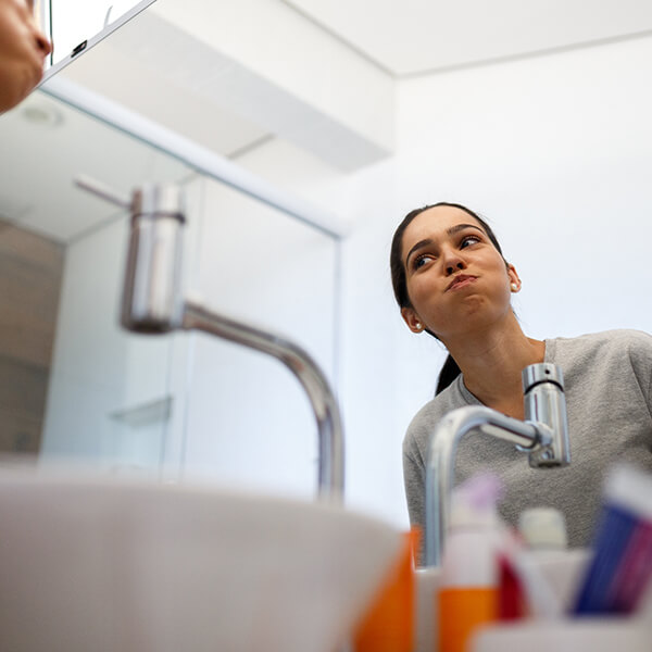 Image of a woman in front of a mirror washing her mouth with AO Pro Products