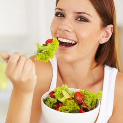 A woman smiling and eating a salad