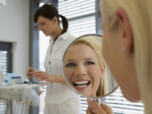 A woman viewing her new smile in a hand mirror