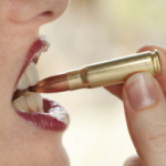 A woman literally biting a bullet