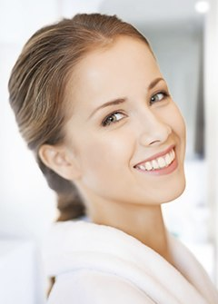 A woman in a spa setting smiling to show how Botox & Dermal Fillers are a great way to eliminate wrinkles.