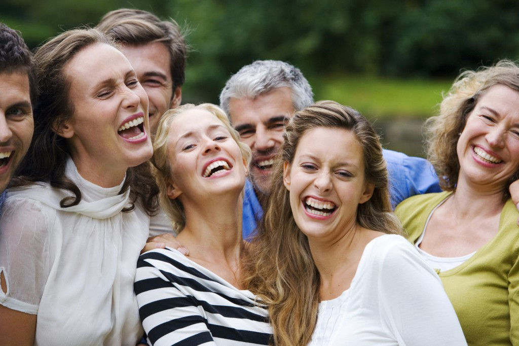 A group of men and woman laughing and smiling