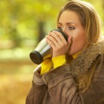 A woman outside in the fall weather drinking coffee
