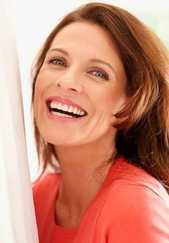 A woman smiles to show how full mouth rehabilitation can repair your smile.