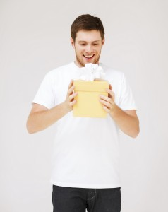A man excitedly holding a present.