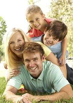 A smiling family playing in the grass illustrates how our dentists in Minneapolis keep patients smiling.