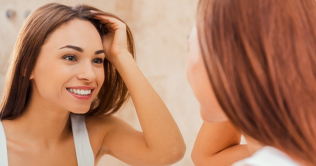 girl looking at her dental bonding in mirror