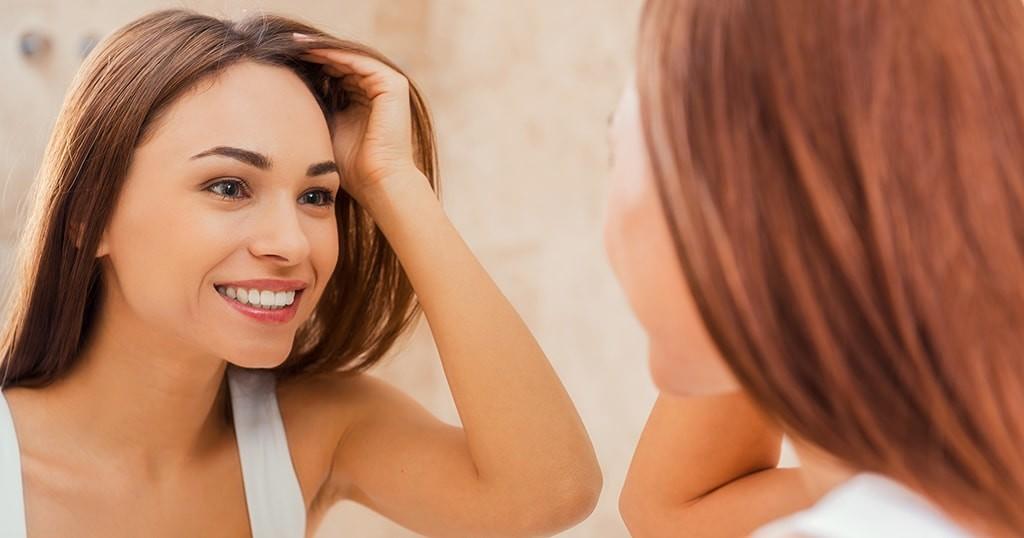 girl looking at her dental bonding in mirror