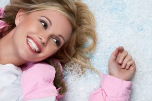 A woman laying in the snow smiling