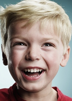 A young patient smiles to show how our Family Dentist in Minneapolis keeps your whole family smiling