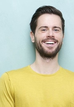 A man in a yellow sweater smiles to show how porcelain veneers from our Minneapolis dentist can brighten your smile.